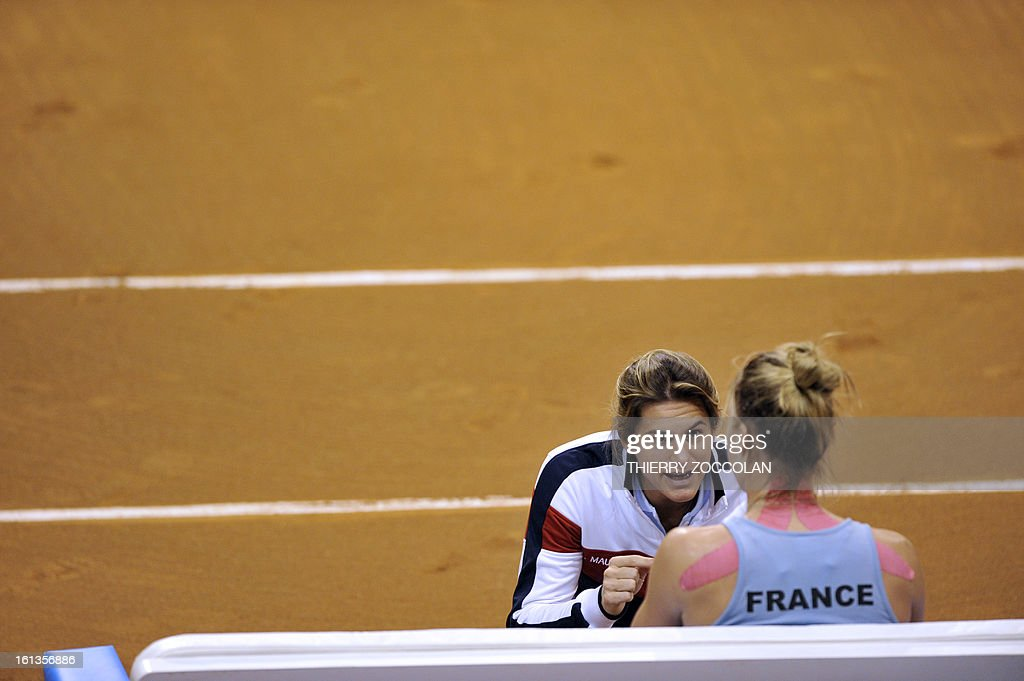 France's coach Amelie Mauresmo (L) talks to Pauline Parmentier during her Fed Cup 2013 tennis match against Germany's Julia Goerges on February 10, 2013 at the Beaublanc courts in Limoges. Germany completed a 3-0 win over France in a Fed Cup World Group II tie today when Julia Goerges defeated Pauline Parmentier 6-4, 6-2.