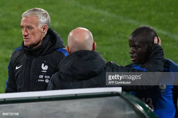 France's coach Didier Deschamps looks on as France's defender N'golo Kante is comforted by a coaching staff member after he was substituted during...