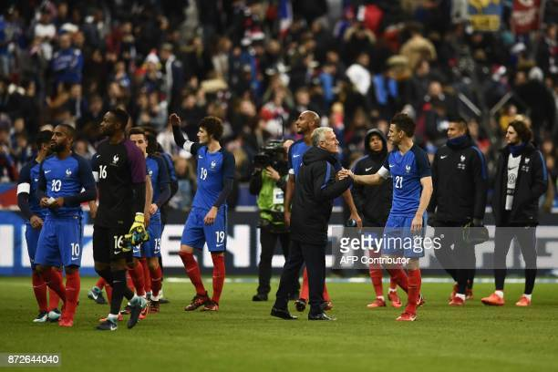 France's coach Didier Deschamps shakes hands with France's defender Laurent Koscielny as France's team players celebrate after winning at the end of...