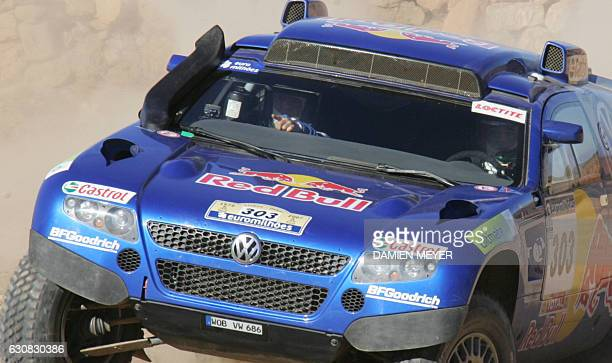 France's codriver Michel Perin shows the way to teammate Spaniard Carlos Sainz to win the third stage of the 29th Dakar between Nador and Er Rachidia...