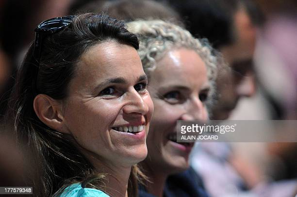 France's Culture minister Aurelie Filippetti shares a laugh with former Ecology minister Delphine Batho as they attend a plenary session on the...