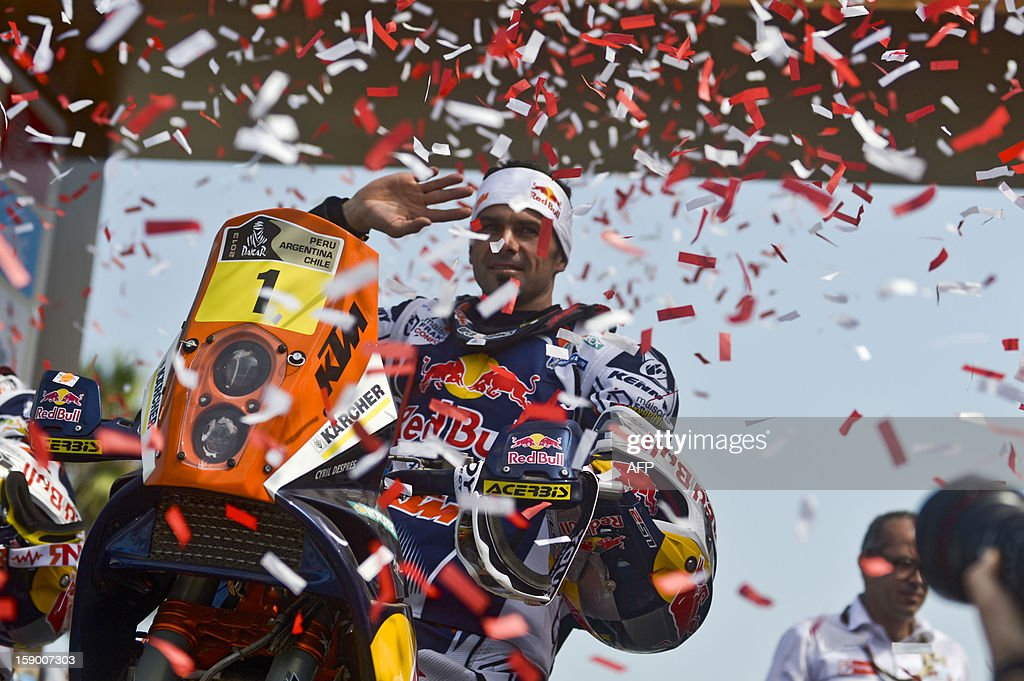 France's Cyril Despres, winner of the 2012 Dakar Rally, waves as he arrives to the podium in his KTM during the departure ceremony of the fifth South American edition of the Dakar Rally 2013 in Lima on January 5, 2013. AFP PHOTO /ERNESTO BENAVIDES