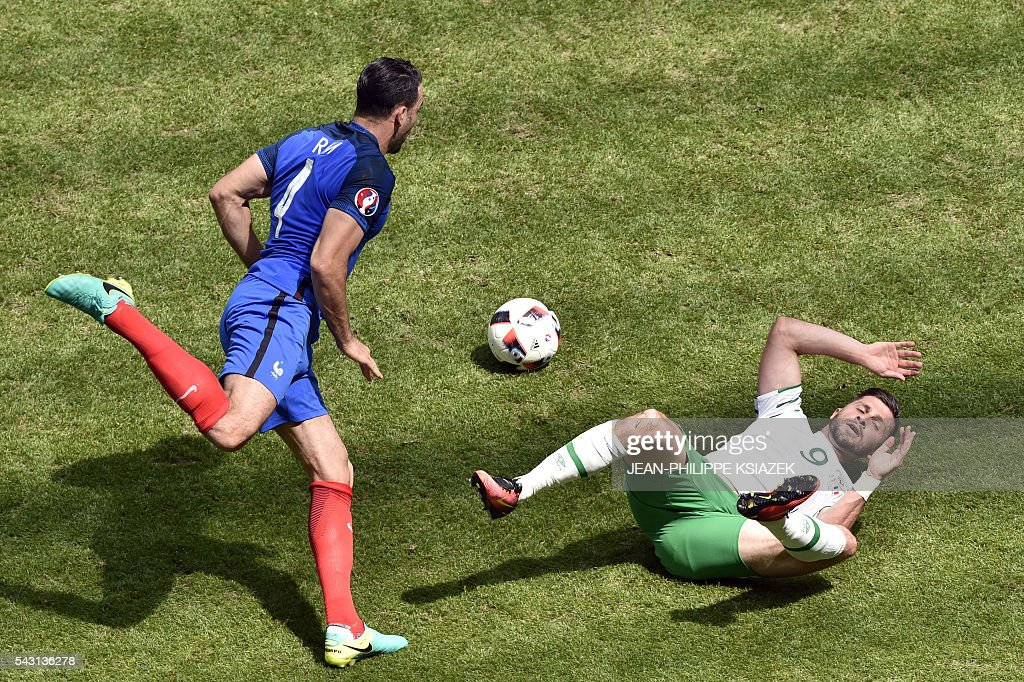 France's defender Adil Rami (L) and Ireland's forward Shane Long vie for the ball during the Euro 2016 round of 16 football match between France and Republic of Ireland at the Parc Olympique Lyonnais stadium in Décines-Charpieu, near Lyon, on June 26, 2016. / AFP / JEAN