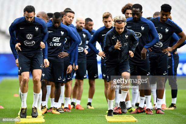 TOPSHOT France's defender Adil Rami France's forward Antoine Griezmann and teammates attend a training session at the Stade de France stadium in...