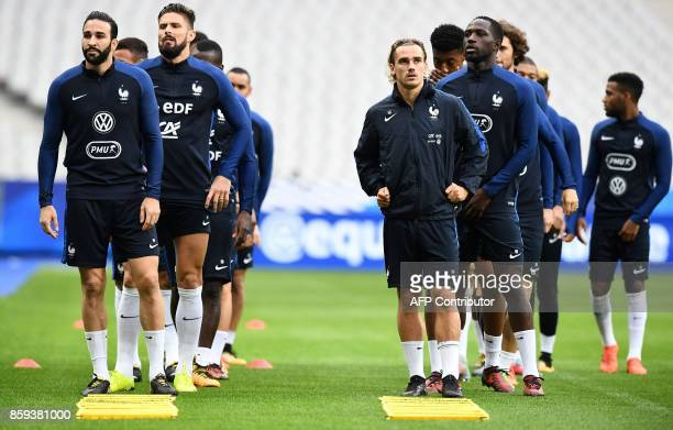France's defender Adil Rami France's forward Antoine Griezmann and teammates attend a training session at the Stade de France stadium in SaintDenis...