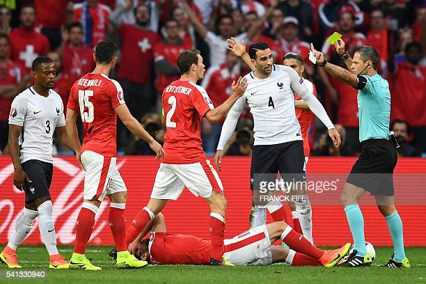 TOPSHOT France's defender Adil Rami receives a yellow card from Slovenian referee Damir Skomina as Switzerland's forward Admir Mehmedi lies on the...
