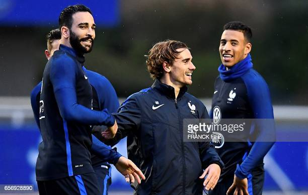 France's defender Adil Rami shares a laugh with France's forward Antoine Griezmann and France's midfielder Corentin Tolisso during a training session...