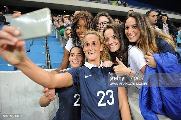 France's defender Amel Majri and France's midfielder Kheira Hamraoui take a selfie with supporters after the Women's friendly football match France...