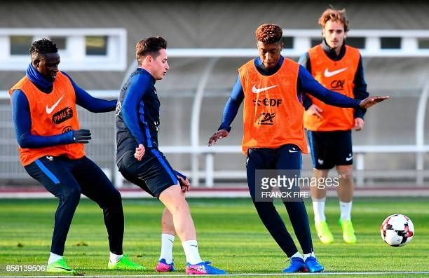 France's defender Benjamin Mendy forward Florian Thauvin and defender Presnel Kimpembe take part in a training session in Clairefontaine near Paris...
