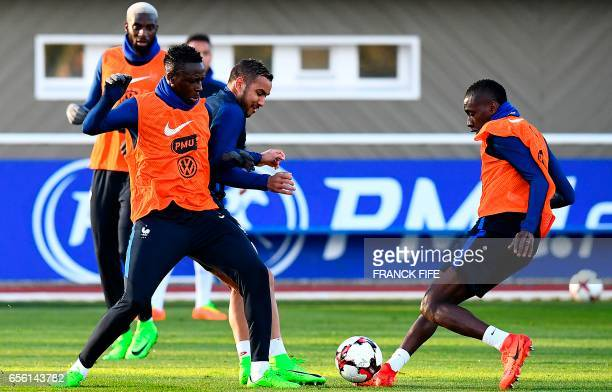 France's defender Benjamin Mendy vies with forward Dimitri Payet as midfielder Blaise Matuidi controls the ball during a training session in...