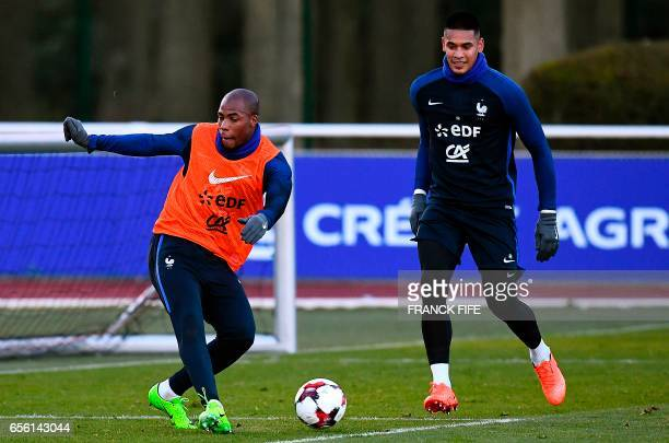 France's defender Djibril Dembele vies with France's goalkeeper Alphonse Areola during a training session in Clairefontaine near Paris on March 21 as...