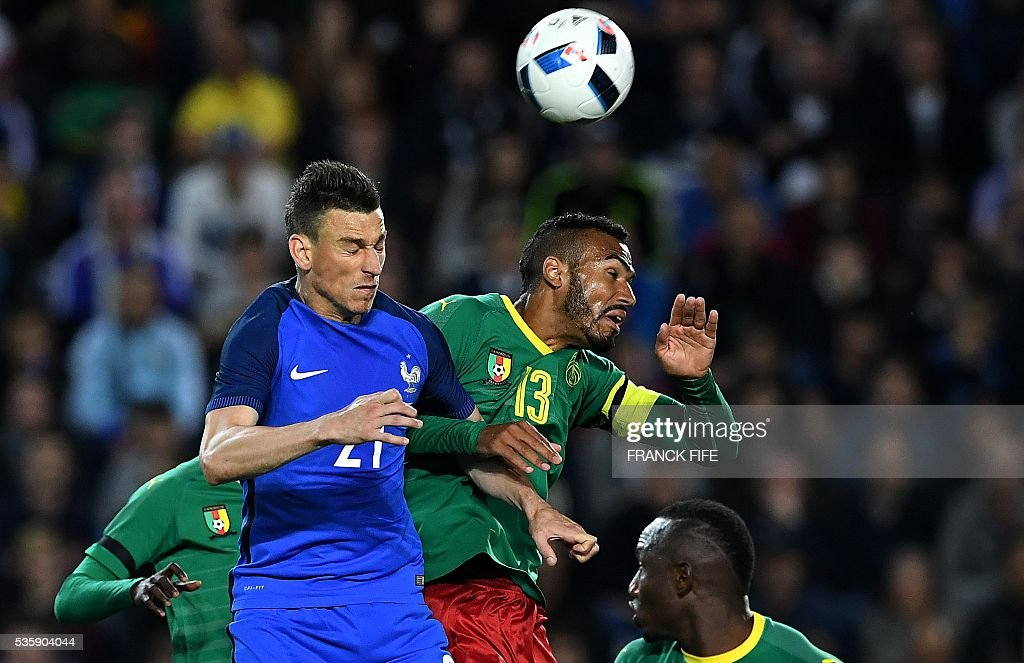 France's defender Laurent Koscielny (L) and Cameroon's forward Eric Maxim Choupo-Moting head the ball during the International friendly football match between France and Cameroon at the Beaujoire stadium, in Nantes, western France, on May 30, 2016 as part of the French team's preparation for the upcoming Euro 2016 European football championships. / AFP / FRANCK