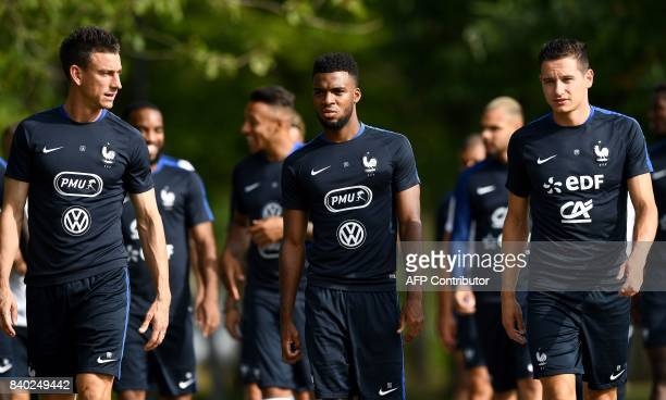 France's defender Laurent Koscielny forward Thomas Lemar and forward Florian Thauvin arrive for a training session in Clairefontaine en Yvelines on...