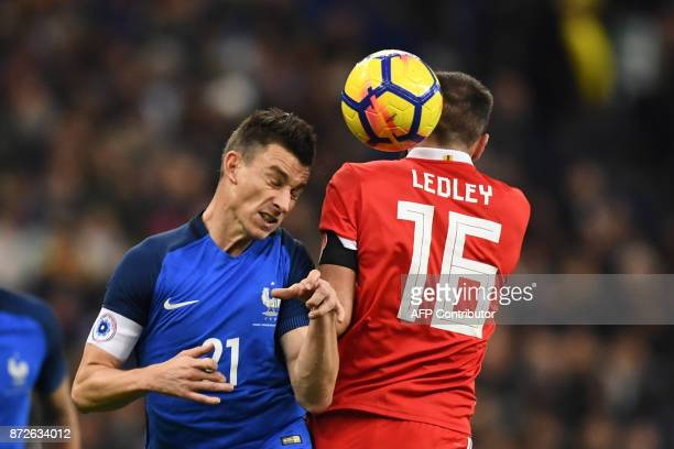 France's defender Laurent Koscielny heads the ball with Wales' midfielder Joe Ledley during the friendly football match between France and Wales at...