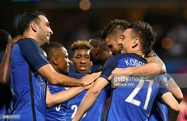 France's defender Laurent Koscielny is congratuled by France's defender Adil Rami and France's forward Olivier Giroud during the friendly football...
