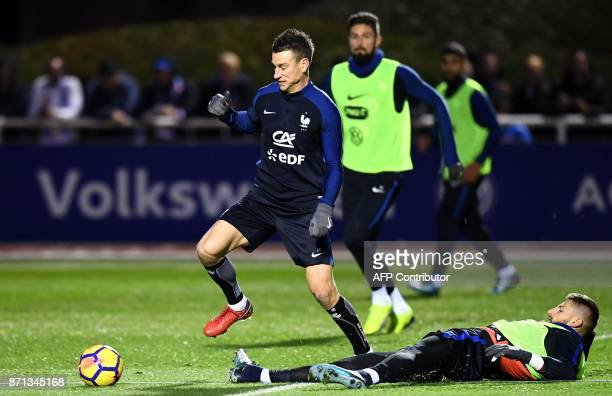 France's defender Laurent Koscielny is tackled by France's goalkeeper Benoit Costil during a training session in ClairefontaineenYvelines near Paris...