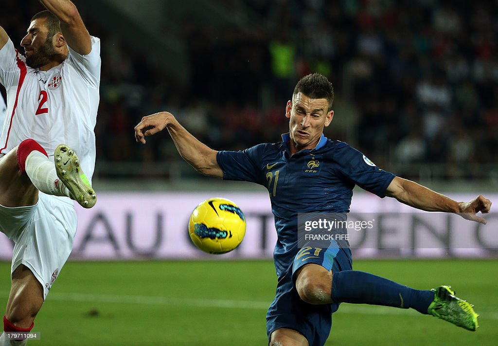France's defender Laurent Koscielny (R) kicks the ball next to Georgia's defender Ucha Lobjanidze during the FIFA World Cup 2014 qualifying football match Georgia vs France on September 6 2013 at the Boris Paichadze stadium in Tbilisi.