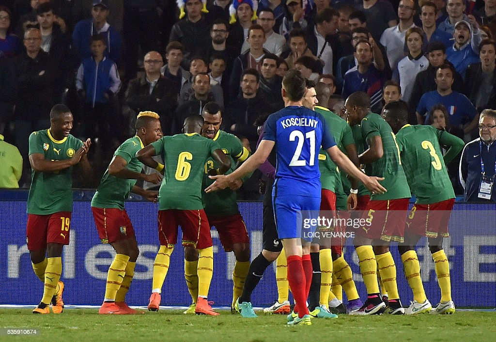 France's defender Laurent Koscielny reacts as Cameroonian players celebrate after scoring a goal during the International friendly football match between France and Cameroon at the Beaujoire stadium, in Nantes, western France, on May 30, 2016 as part of the French team's preparation for the upcoming Euro 2016 European football championships. / AFP / LOIC