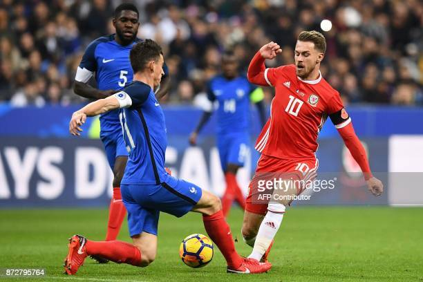 France's defender Laurent Koscielny vies for the ball with Wales' mdifielder Aaron Ramsey during the friendly football match between France and Wales...