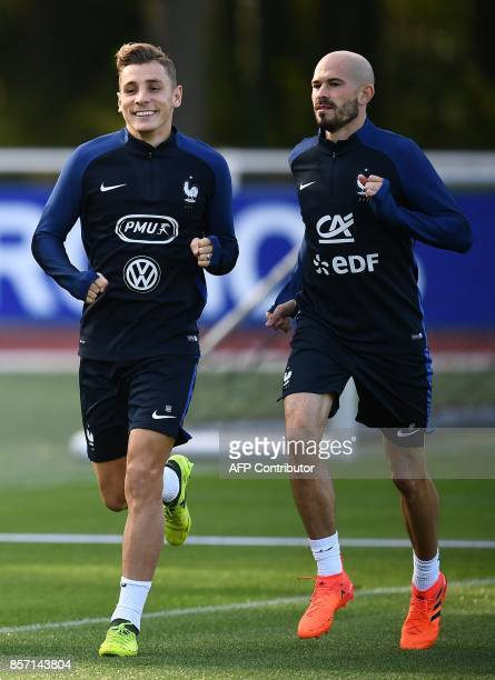 France's defender Lucas Digne and France's defender Christophe Jallet run during a training session in ClairefontaineenYvelines on October 3 in...