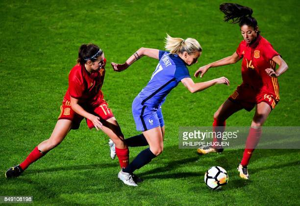 France's defender Marion Torrent dribbles between Spain's forward Mariona Caldentey and Spain's defender Leila Ouahabi during a friendly football...