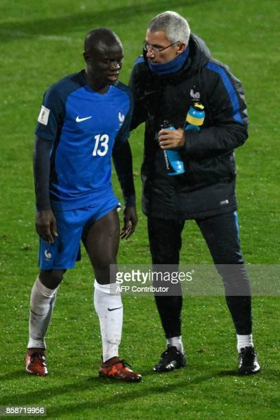 France's defender N'golo Kante is comforted by a coaching staff member after he was substituted during the FIFA World Cup 2018 qualifying football...