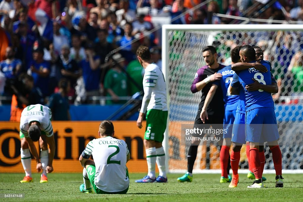 TOPSHOT - France's defender Patrice Evra (R) hugs France's forward Dimitri Payet (2R) after winning the Euro 2016 round of 16 football match between France and Republic of Ireland at the Parc Olympique Lyonnais stadium in Decines-Charpieu, near Lyon, on June 26, 2016. / AFP / MARTIN