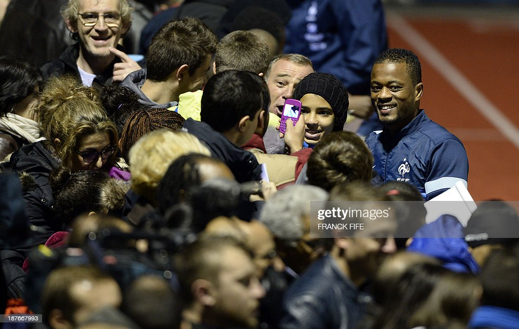 France's defender Patrice Evra (R) signs autographs before a training session in Clairefontaine-en-Yvelines, outside Paris, on November 11, 2013, ahead of the two-legged World Cup 2014 qualifying play-off against Ukraine.