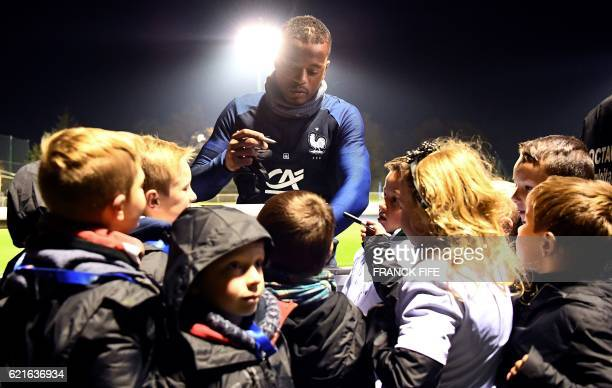 TOPSHOT France's defender Patrice Evra signs autographs before a training session in ClairefontaineenYvelines near Paris on November 7 as part of the...