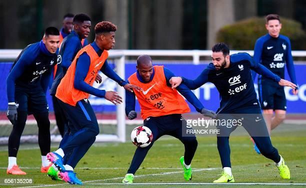 France's defender Presnel Kimpembe France's defender Djibril Sidibe and defender Adil Rami take part in a training session in Clairefontaine near...