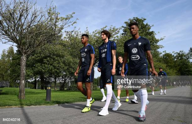 France's defender Presnel Kimpembe midfielder Adrien Rabiot and forward Kyngsley Coman arrive to a training session in Clairefontaine en Yvelines on...