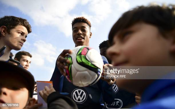 France's defender Presnel Kimpembe signs autographs before a training session as part of the team's preparation for the upcoming friendly football...