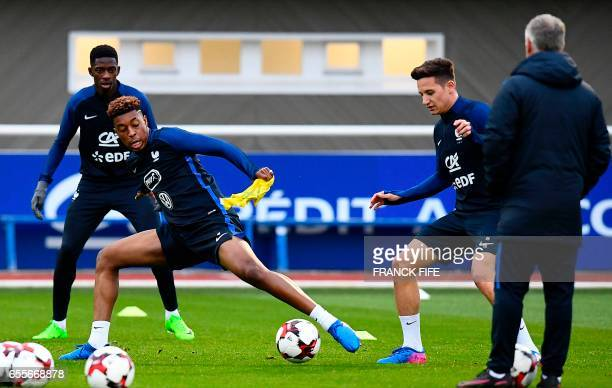 France's defender Presnel Kimpembe vies with forward Florian Thauvin in front of France's head coach Didier Deschamps during a training session in...