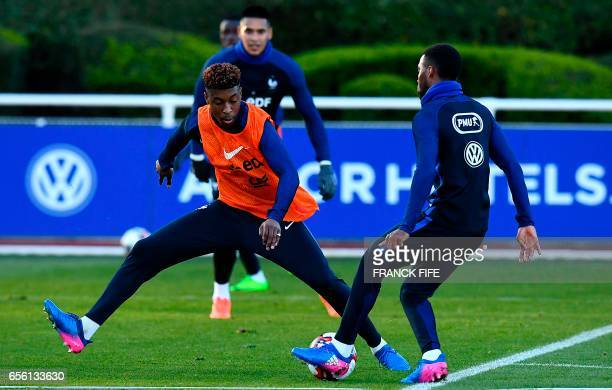 France's defender Presnel Kimpembe vies with midfielder Thomas Lemar during a training session in Clairefontaine near Paris on March 21 as part of...