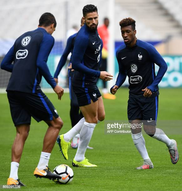 France's defender Raphael Varane France's forward Olivier Giroud and France's forward Kingsley Coman attend a training session at the Stade de France...