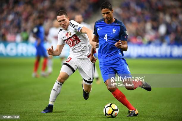 France's defender Raphael Varane vies for the ball with Belarus' forward Anton Saroka during the FIFA World Cup 2018 qualification football match...