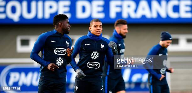 France's defender Samuel Umtiti and forward Kylian Mbappe run during a training session in Clairefontaine near Paris on March 21 as part of the...