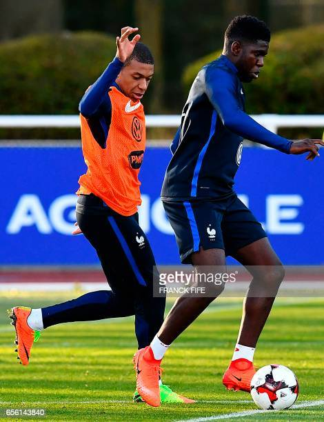 France's defender Samuel Umtiti vies with forward Kylian Mbappe during a training session in Clairefontaine near Paris on March 21 as part of the...