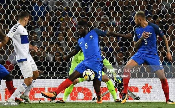 France's defender Samuel Umtiti vies with Luxembourg's midfielder Danel Sinani next to France's defender Layvin Kurzawa during the FIFA World Cup...