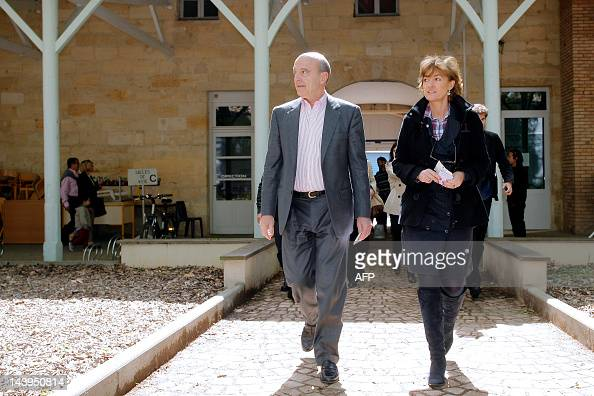 France's Defense minister Alain Juppe arrives with his wife Isabelle on May 6 2012 in a polling station in Bordeaux southwestern France as part of...