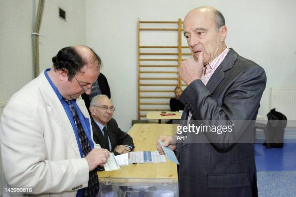 France's Defense minister Alain Juppe prepares to cast his ballot on May 6 2012 in a polling station in Bordeaux southwestern France as part of the...