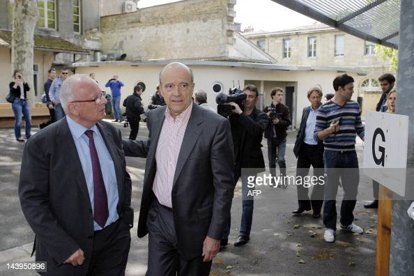 France's Defense minister Alain Juppe speaks with Bordeaux' mayor deputy Hugues Martin outside a polling station on May 6 2012 in Bordeaux...