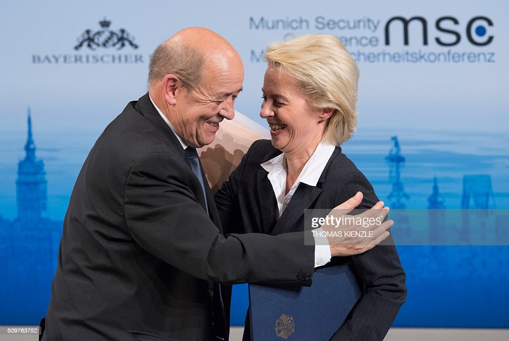 France's Defense Minister Jean-Yves Le Drian (L) embraces his German counterpart Ursula von der Leyen after they participated in a panel discussion at the 52nd Munich Security Conference (MSC) in Munich, southern Germany, on February 12, 2016. / AFP / THOMAS KIENZLE