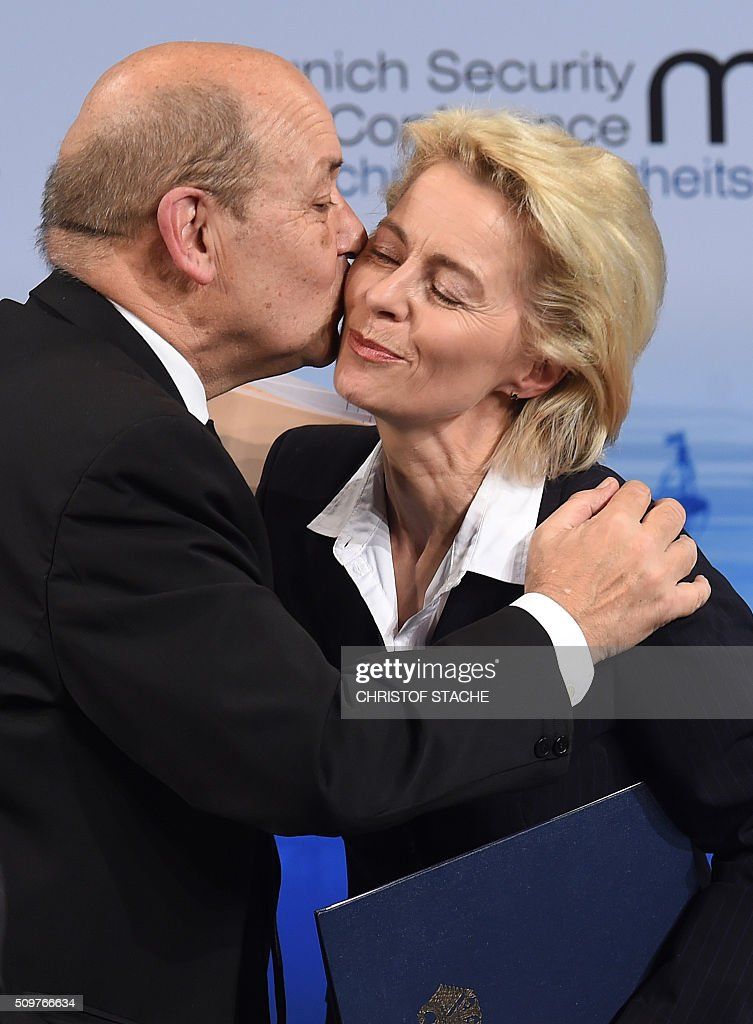 France's Defense Minister Jean-Yves Le Drian (L) embraces his German counterpart Ursula von der Leyen (R) after they participated in a panel discussion at the 52nd Munich Security Conference (MSC) in Munich, southern Germany, on February 12, 2016. / AFP / Christof STACHE