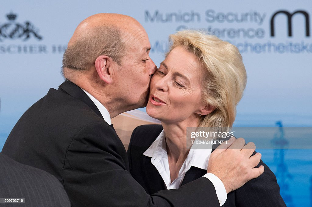 France's Defense Minister Jean-Yves Le Drian (L) kisses his German counterpart Ursula von der Leyen after they participated in a panel discussion at the 52nd Munich Security Conference (MSC) in Munich, southern Germany, on February 12, 2016. / AFP / THOMAS KIENZLE