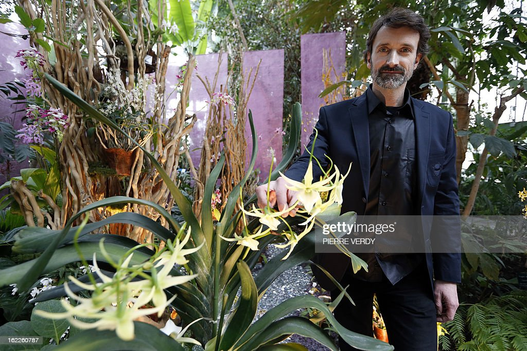 France's Denis Larpin, botanist of the 'Mille et une orchidees' (1,001 orchids) exhibition organized at the Jardin des Plantes in Paris, poses on February 21, 2013 in front of flowers that are part of the Jardin du Luxembourg collection. The event runs from February 22 to March 23, 2013. AFP PHOTO PIERRE VERDY