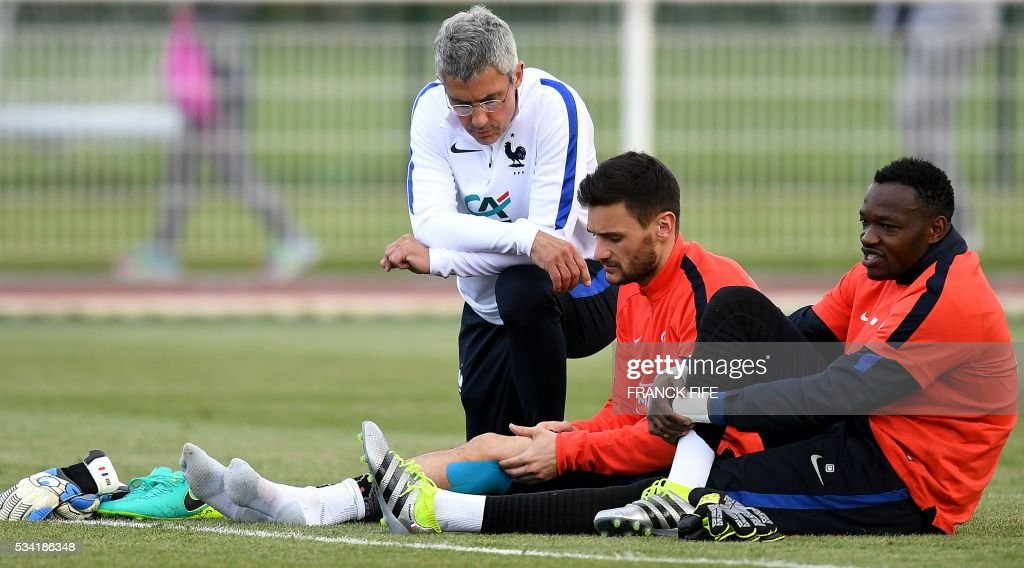 France's doctor Franck Le Gall (L) speaks with France's goalkeepers Hugo Lloris (C) and Steve Mandanda (R) at the end of a training session in Clairefontaine as part of the team's preparation for the upcoming Euro 2016 European football championships, on May 25, 2016. / AFP / FRANCK