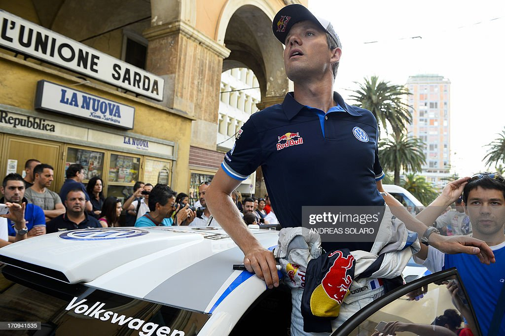 France's driver Sebastian Ogier looks on near his Volkswagen Polo WRC, during the opening ceremony of the FIA World Rally Championship of Italy in Sassari, on the Italian island of Sardinia on June 20, 2013.