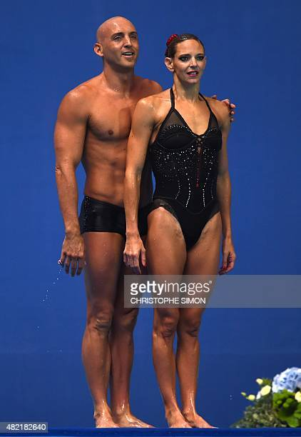 France's duet Virginie Dedieu and Benoit Beaufils wait for their results after competing in the Mixed duet Free preliminary event during the...