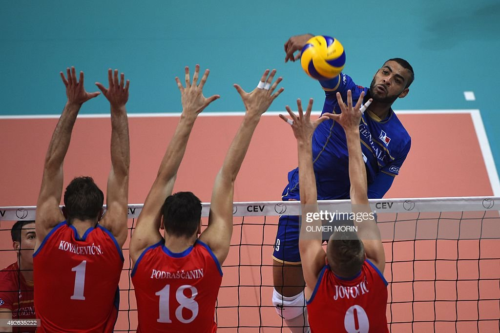 France's Earvin Ngapeth hits a return to Serbia's Marko Podrascanin and Nicola Jovovic during their quarter final volleyball match France vs Serbia...